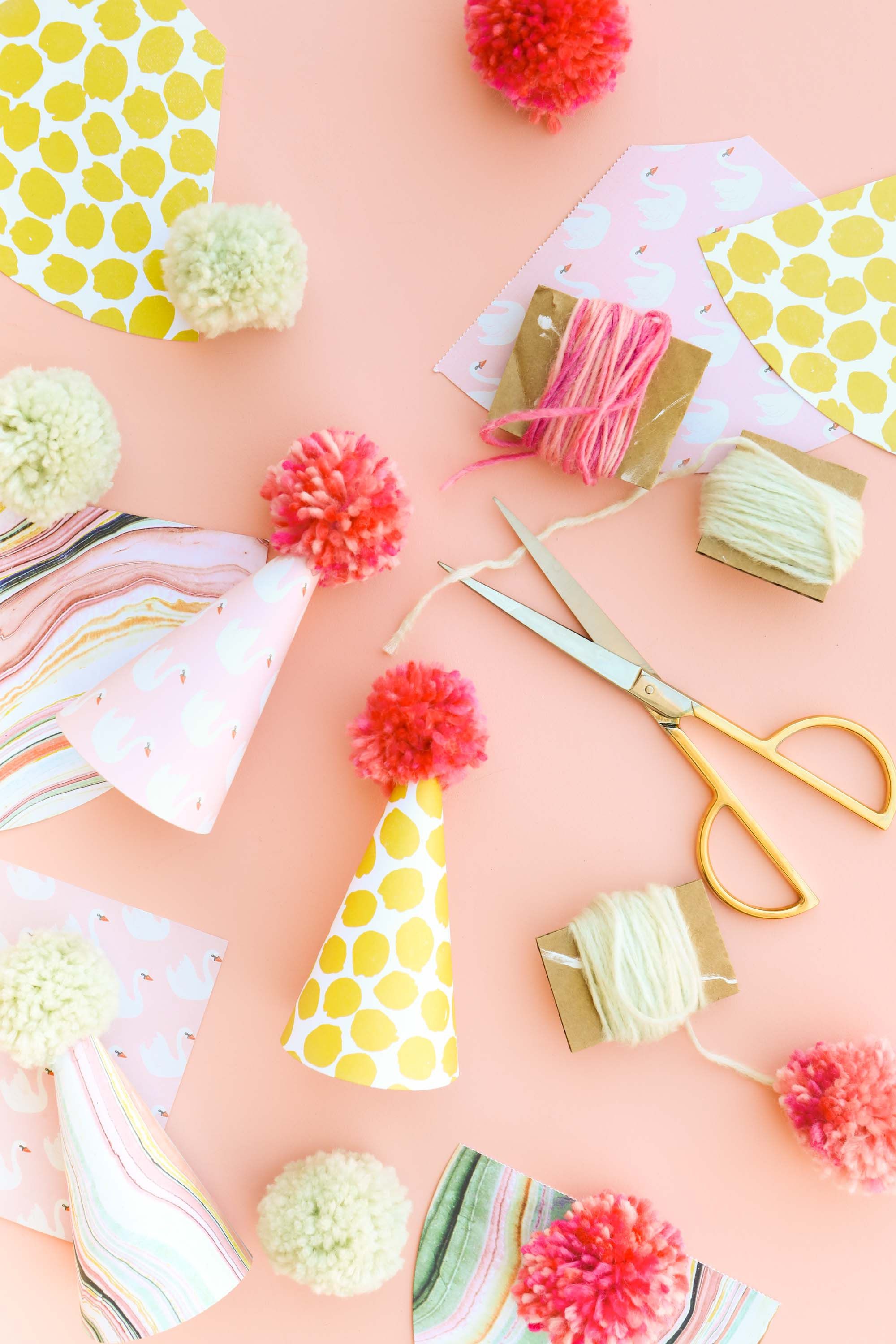 Make Your Own Party Hats Using Scrapbook Paper And Yarn Pom Poms