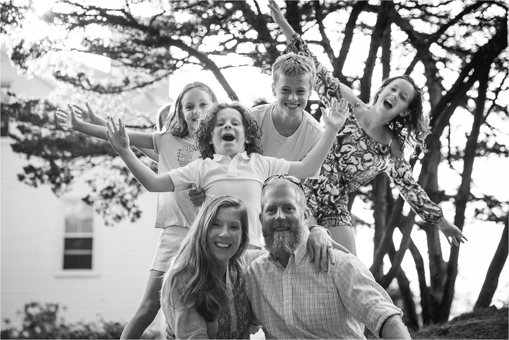Couple's Portrait with kids sneaking up behind them photobomb Kennebunkport Maine Sarah Jane Photography