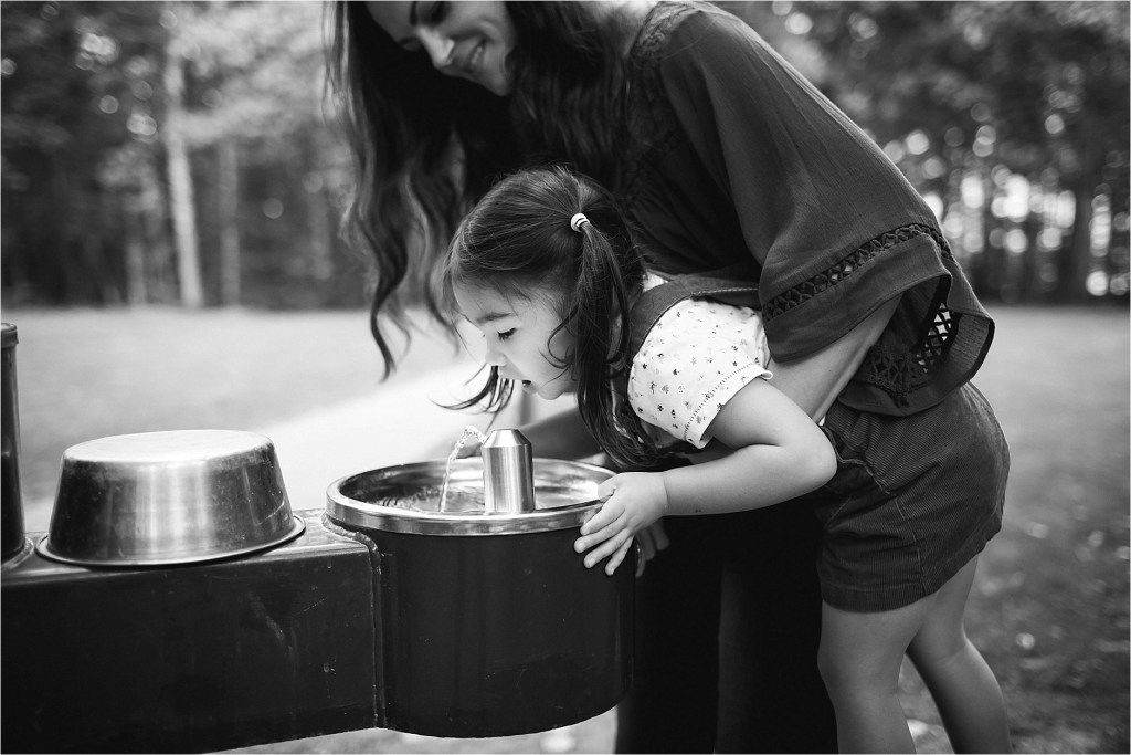 small child drinking from water fountain, black and white photo, family lifestyle photo session
