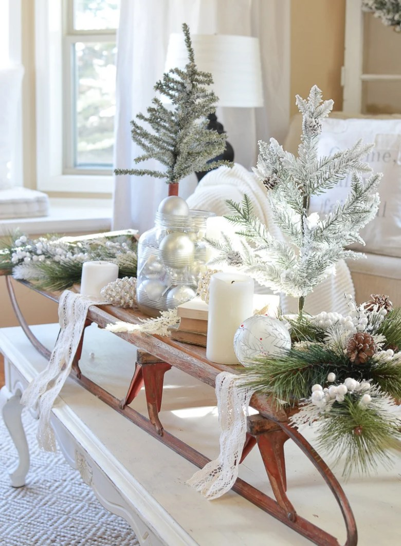 Farmhouse style Christmas decor. Vintage sled on coffee table with Christmas trees and greenery!