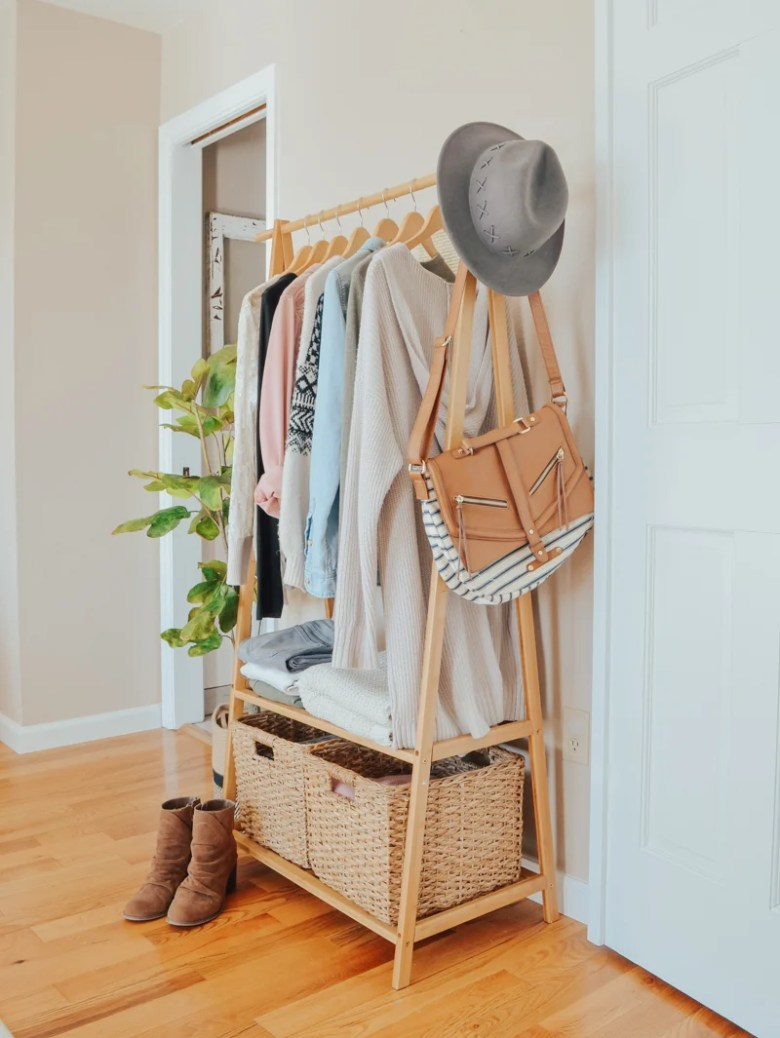 An Easy Storage Solution for a Small Closet. Bamboo clothing rack in bedroom for extra clothing storage.