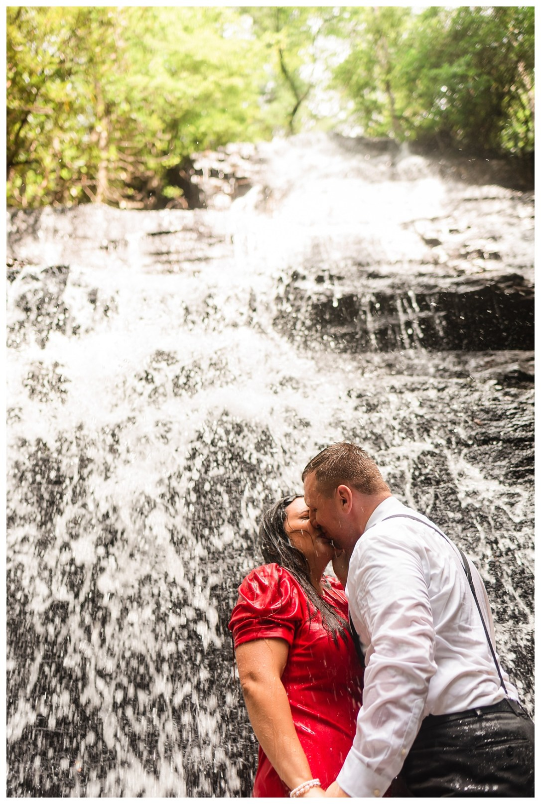 engaged couple kissing under benton waterfall