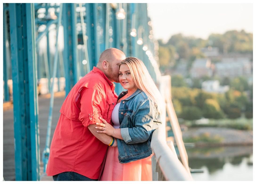 engaged couple embraces on bridge