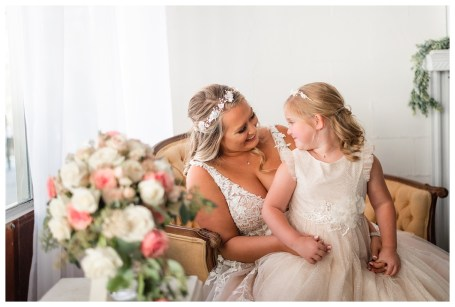 bride and flower girl share a moment