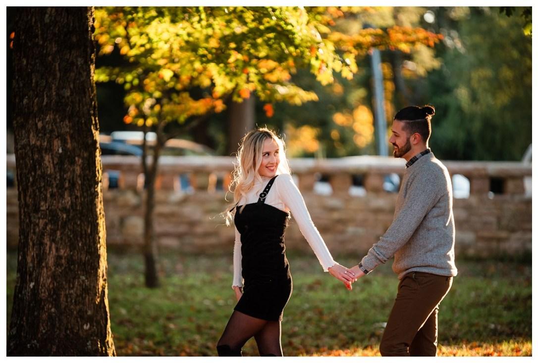 engaged couple walks through park for photos