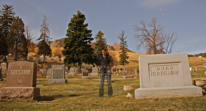 A person standing in a graveyard. It's a long exposure so the person looks a little transparent.