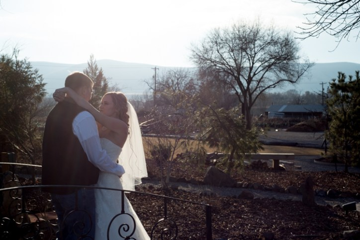 A bride and groom highlighted by the sun outside