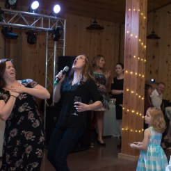 Adults singing dramatically into microphone while children watch