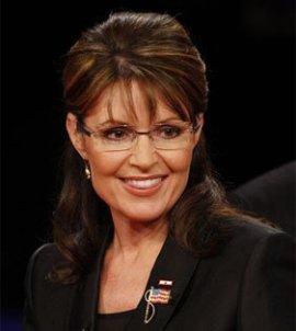Sarah smiling in black suite with flag pin - closeup