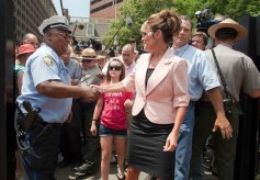 Sarah shakes policeman's hand in Philadelphia as Piper approaches