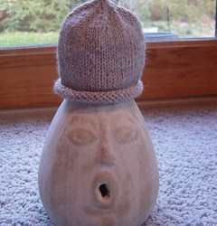 Example of a tiny rolled hat, knit in a neutral colored yarn displayed on a ceremic gourd shaped item with a face.