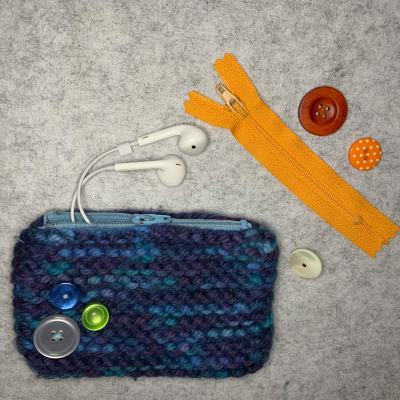 knit pouch with zipper installed and button embellishment, zipper and 3 buttons laid flat. wired earbuds are shown peeking out of the half zipped pouch
