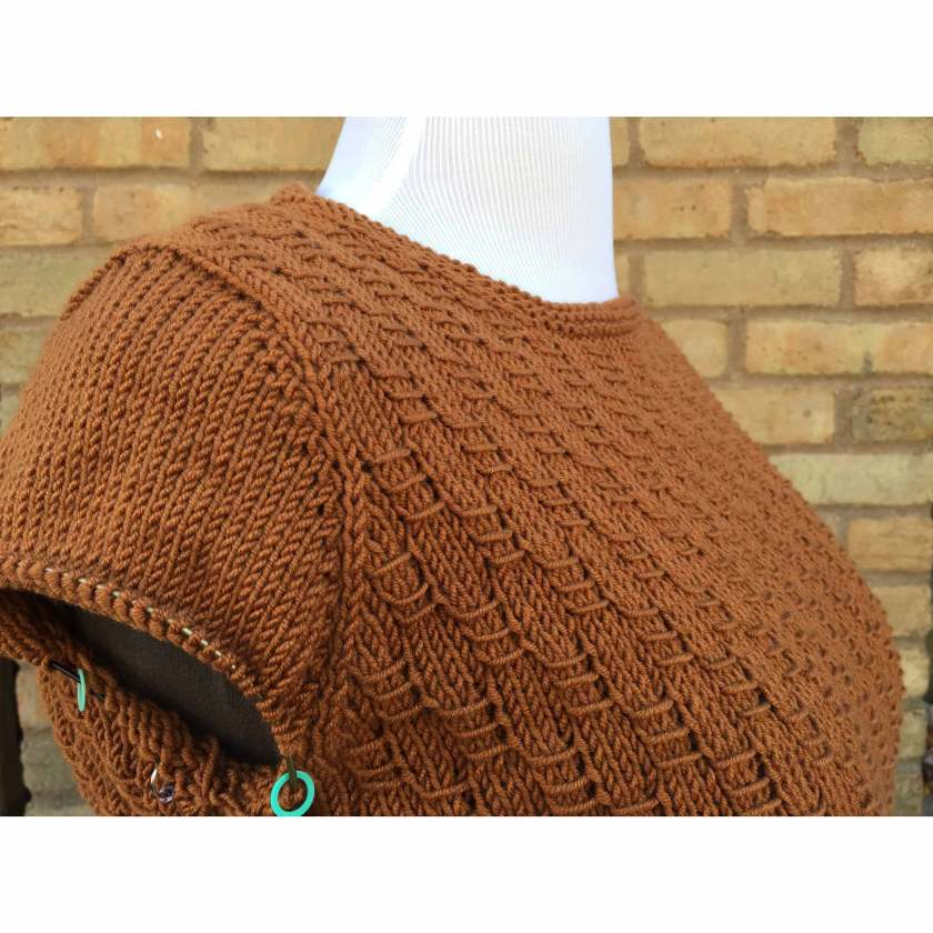 Brown knit sweater shown on dress form, knitting in progress. :Sleeve cap is complete.