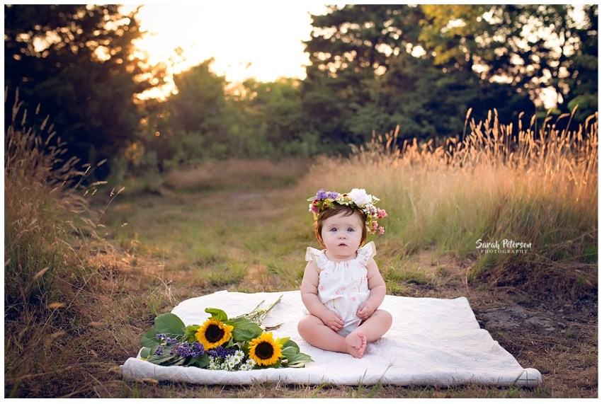 baby girl turning one wearing a wildflower crown sitting on a blanket in the grass