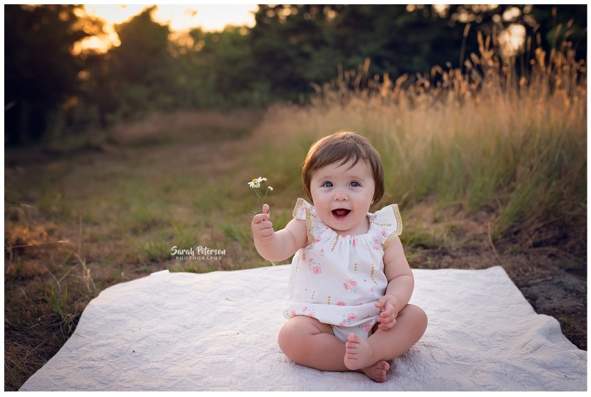 baby girl holding a daisy in her hand
