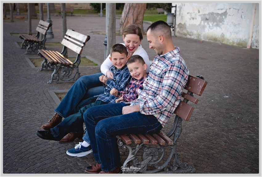 happy family of 4 sitting on a bench laughing in Sorrento Italy