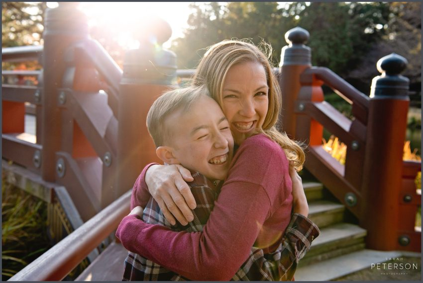 Mom hugging her son with a sun flare behind them standing near a Japanese bridge