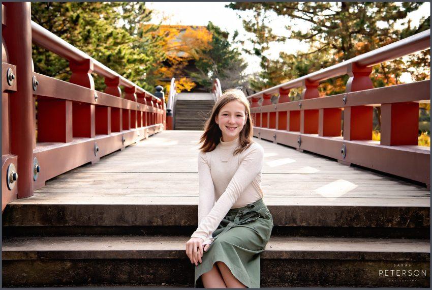Young girl sitting on Japanese bridge
