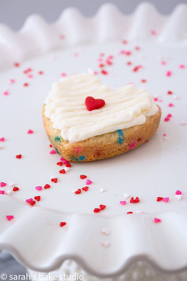 Heart Funfetti Cookie Cake Bars – Love is in the baking with these delightfully chewy, sprinkle filled sugar cookie cake bars topped with fluffy buttercream.
