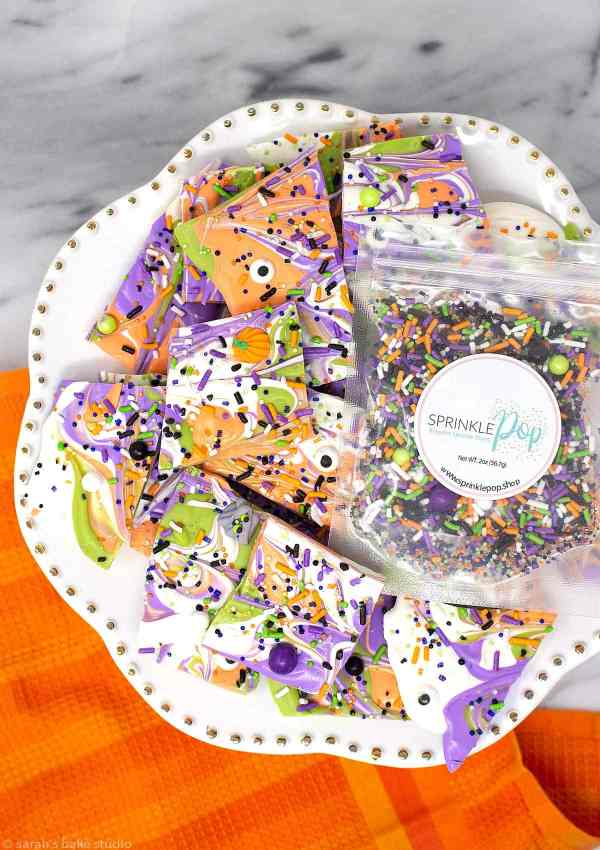 Monster Mash Halloween Bark - brightly colored melted white chocolate swirled together and topped with Sprinkle Pop Monster Mashup Sprinkle Mix makes this monster Halloween chocolate positively spooktacular.