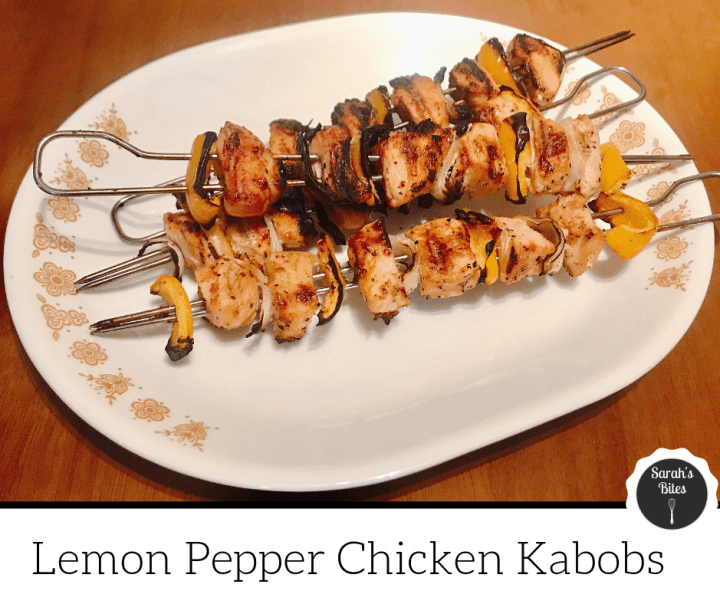 Skewers with chicken, peppers, and onions on a platter