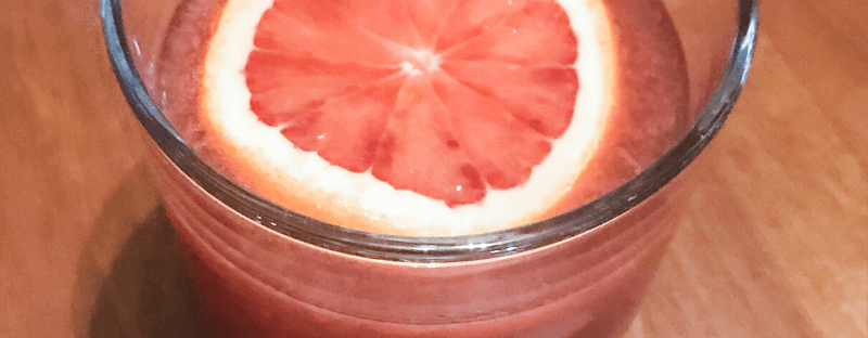 Blood orange pomegranate rum punch - cocktail in glass with floating orange slice