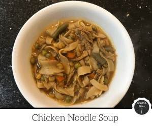 Chicken noodle soup with peas, carrots, and green beans in a bowl