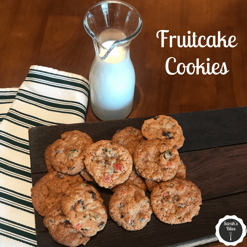 Fruitcake cookies on a wooden serving board next to a bottle of milk