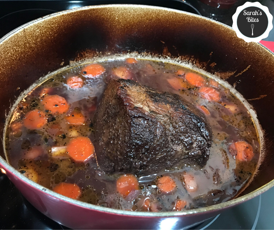 Beef in a dutch oven with carrots, potatoes, and braising liquid