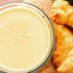 Dish of honey mustard sauce next to chicken tenders