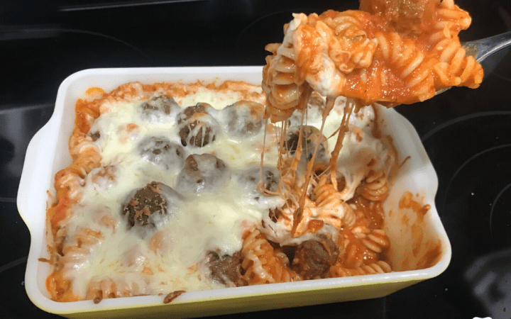 Pasta with cheese and meatballs being spooned out of the baking dish
