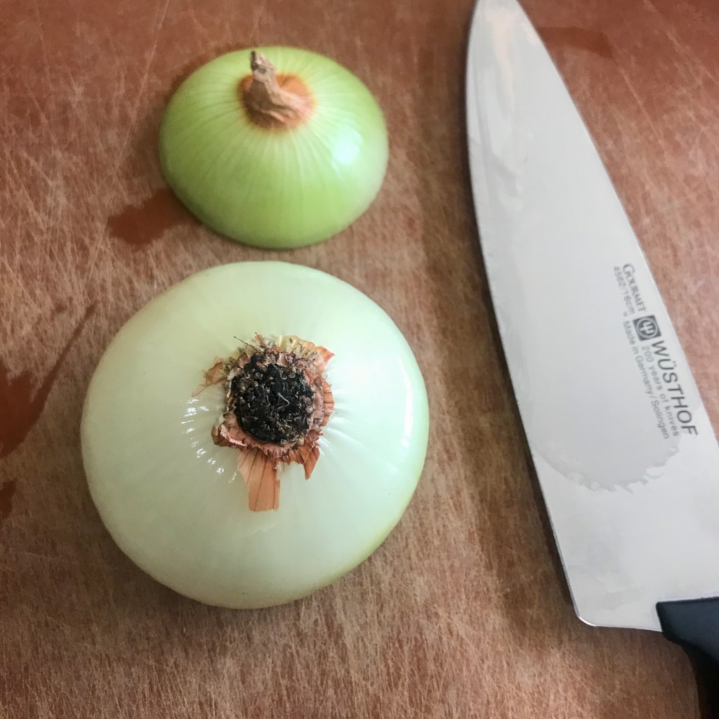 Onion with top cut off on cutting board next to knife