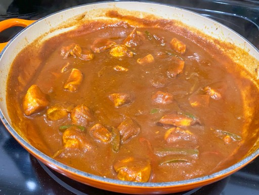Chicken, peppers, and onions with a tomato sauce cooking in a pan