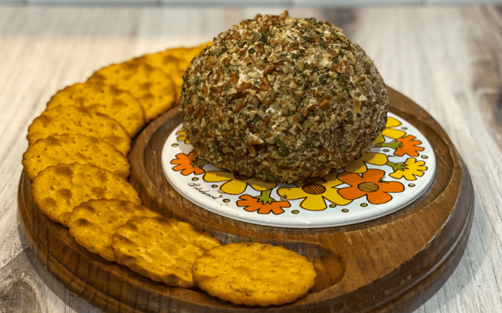 Cheese ball coated in parsley and pecans on a serving plate with crackers.