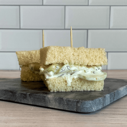 Two small cucumber sandwiches on a small stone block.
