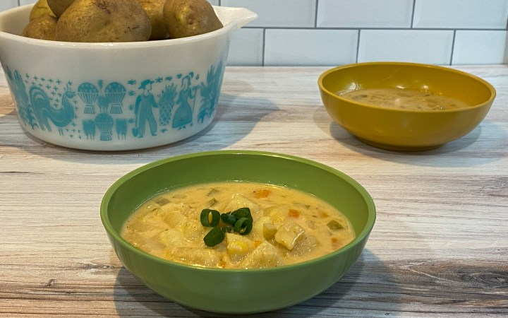 Bowl of potato soup garnished with green onion in front of a bowl of raw potatoes and another bowl of soup.