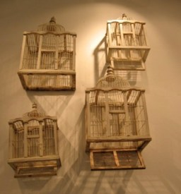 4 vintage bird cages on a wall