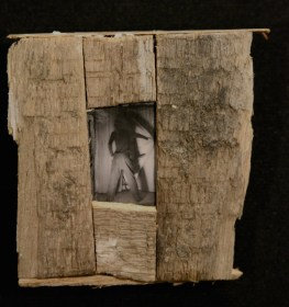 """There Was"" - mixed media object by Sarah Zar. A black and white photograph of a man pulling a curtain open, framed in rustic wood."