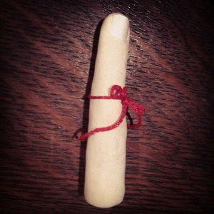 A sculpture of a white finger with a red string tied around it