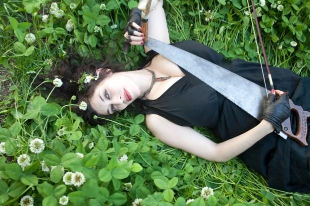 Musical saw player, Sarah Zar in a garden in Brooklyn, NY