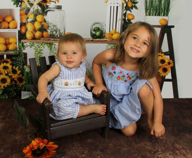 Two children smile, posing together in front of a background of lemons and sunflowers.