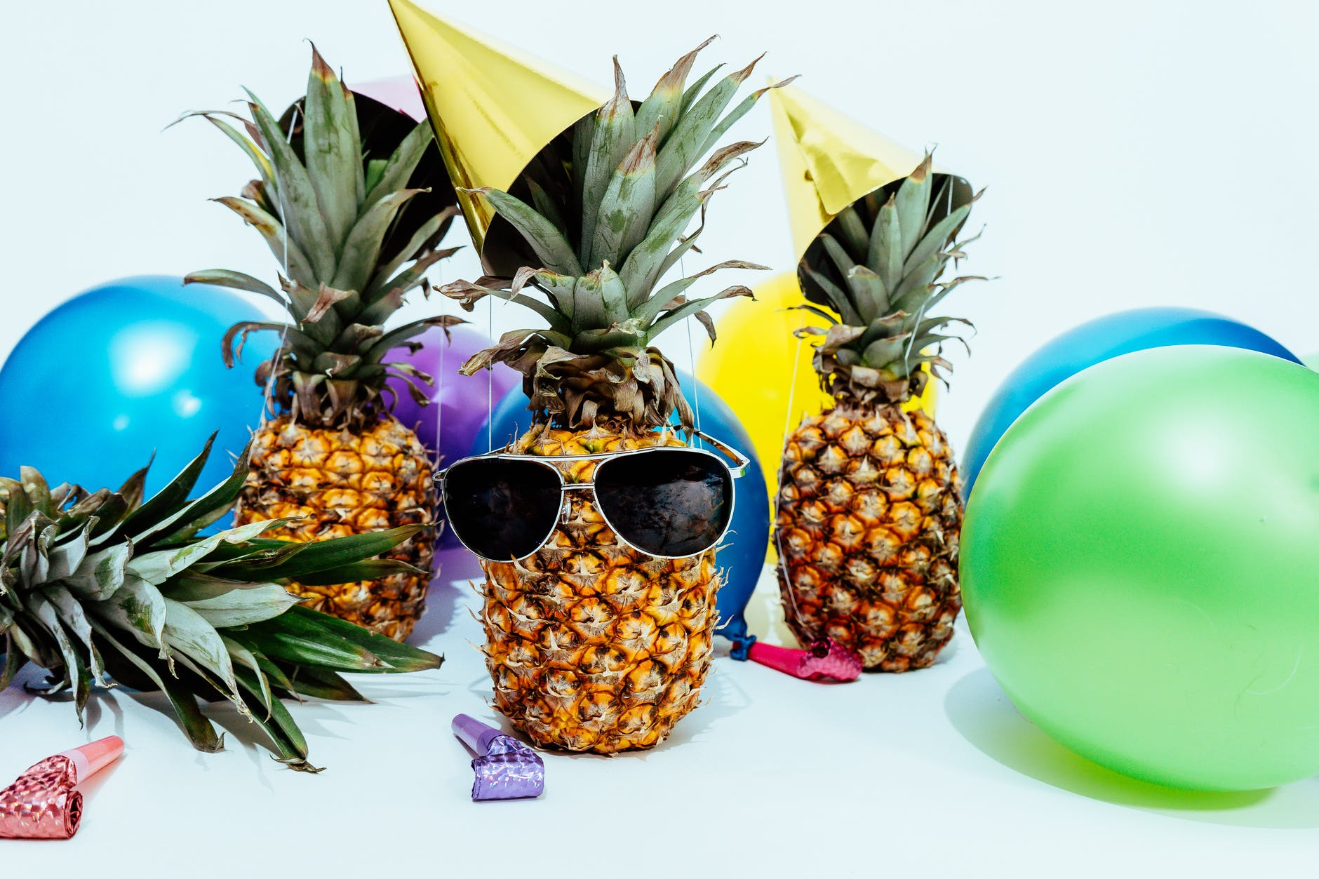 photo of three pineapples surrounded by balloons