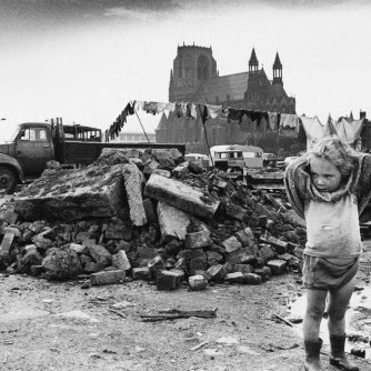 A young traveller girl stands with hands behind her head amid the rubble and dirt of a cleared area of delapidated terraced housing in Manchester. Traveller communities often exploited these areas of open city space which appeared as the result of re-development. Photograph by Shirley Baker Date: 1968