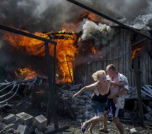 Civilians escape from a fire at a house destroyed by the air attack in the Luhanskaya village