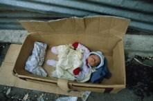 A baby sleeps inside a cardboard box that serves as a cradle.