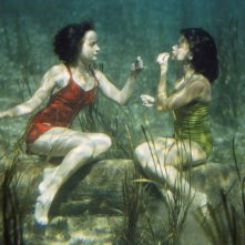 Performing swimmers put on lipstick underwater.