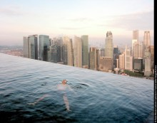 """A man floats in the 57th-floor swimming pool of the Marina Bay Sands Hotel, with the skyline of """"Central,"""" the Singapore financial district, behind him. Singapore"""