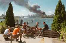 USA. Brooklyn, New York. September 11, 2001. Young people relax during their lunch break along the East River while a huge plume of smoke rises from Lower Manhattan after the attack on the World Trade Center.