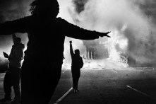 Protestors celebrate as an auto store burns after rioters set fire to numerous businesses throughout the town of Ferguson in the hours following the announcement that a St. Louis grand jury has decided to not indict Darren Wilson, white police officer with the killing of Michael Brown, an unarmed African-American teenager, who's death sparked protests, which often turned violent as demonstrators clashed with a heavily militarized police force. Tuesday, November 25, 2014.