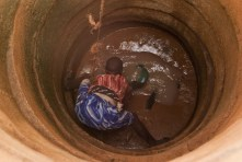 A Tanzanian teenager scoops up muddy water from a well.
